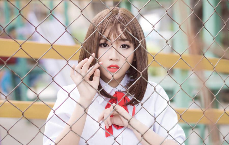 フリー写真 金網のフェンスと制服姿の女子学生