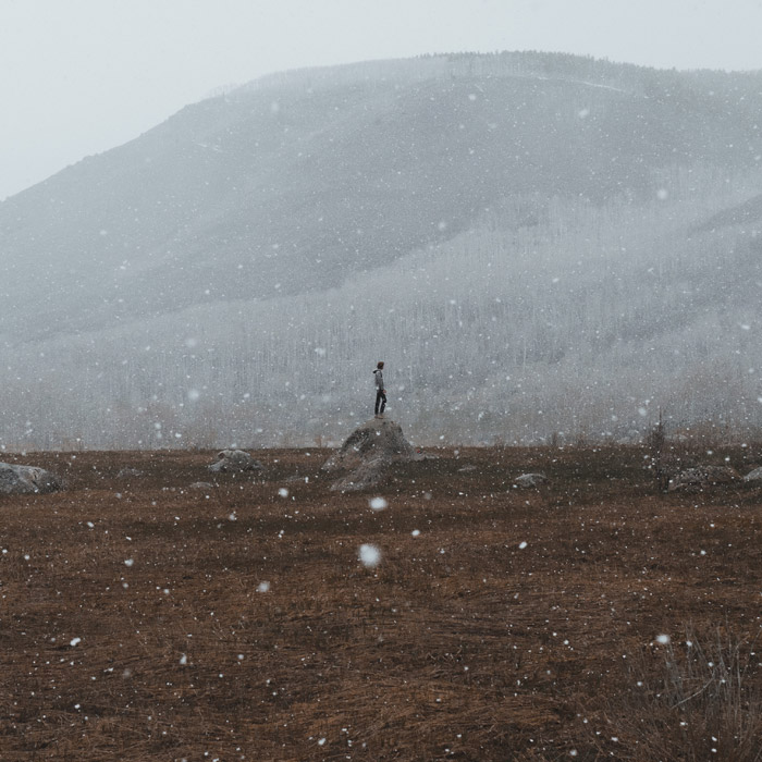 フリー写真 雪が降る中で岩の上に立っている人物