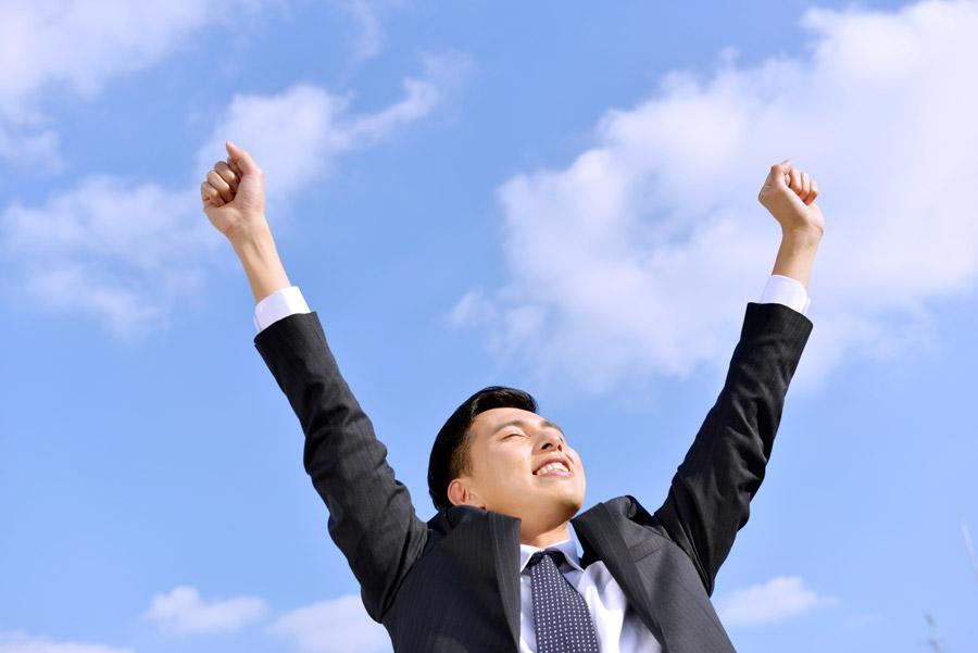 フリー写真 青空の下で背伸びするビジネスマン