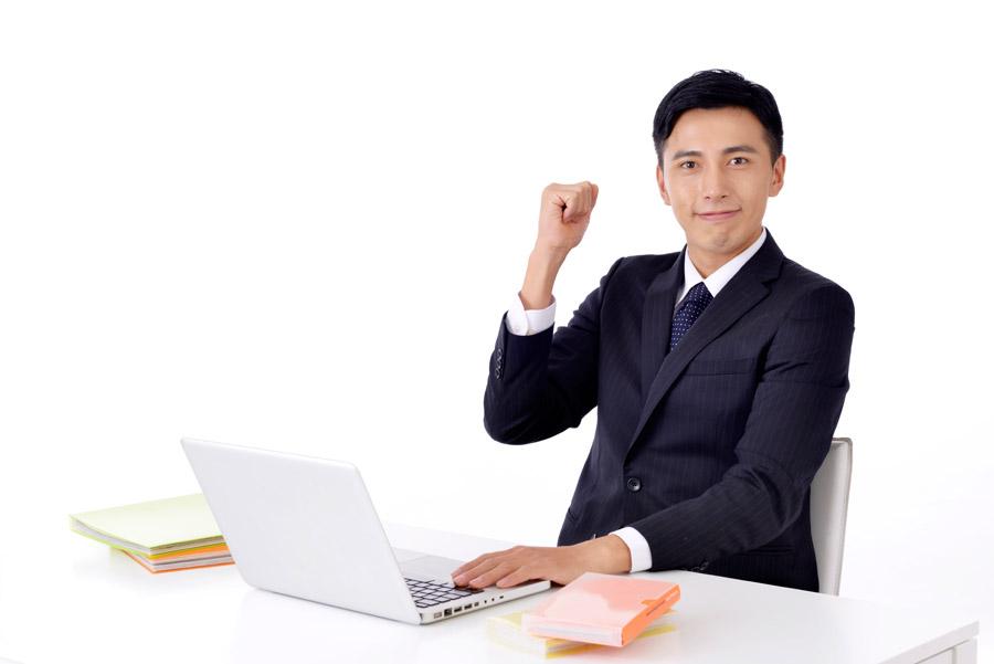 フリー写真 パソコンの前でガッツポーズしているビジネスマン