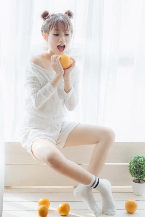フリー写真 オレンジを持って口を開ける女性