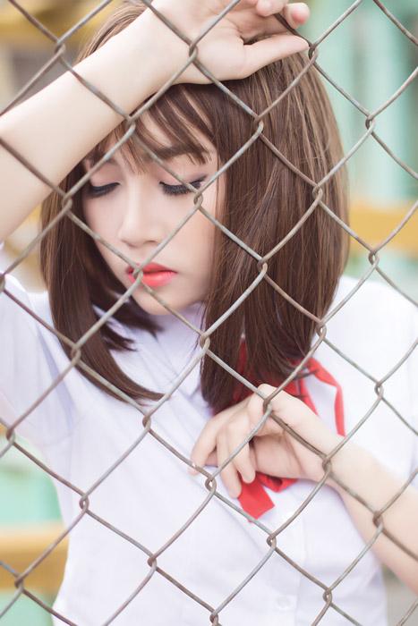 フリー写真 目を閉じてフェンスに寄りかかる女子学生
