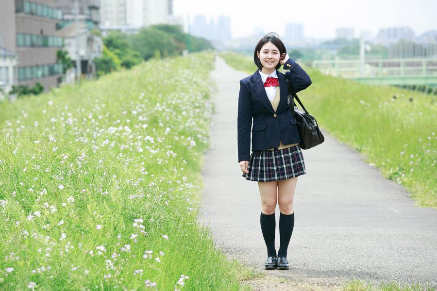 フリー写真 土手を歩いて通学する女子高生