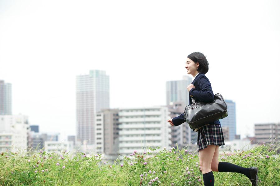 フリー写真 通学鞄を持って学校へ向かう女子高生