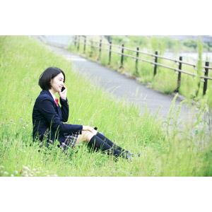 フリー写真, 人物, 少女, アジアの少女, 少女(00212), 学生(生徒), 学生服, 高校生, ブレザー制服, 携帯電話, 通話, 座る(地面), 草むら