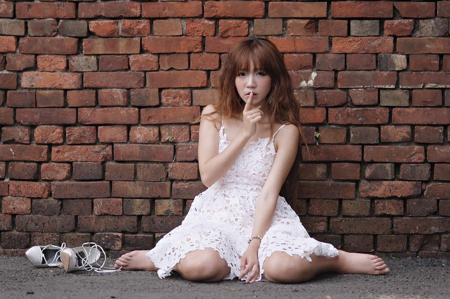 フリー写真 地面に座り込んで「しーっ」のポーズの女性