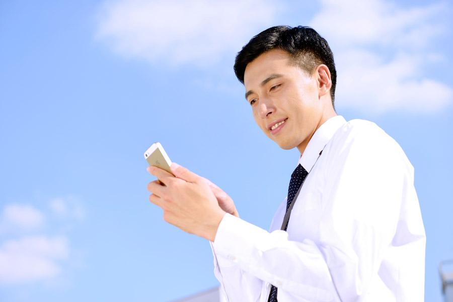 フリー写真 青空の下でスマホを操作しているビジネスマン