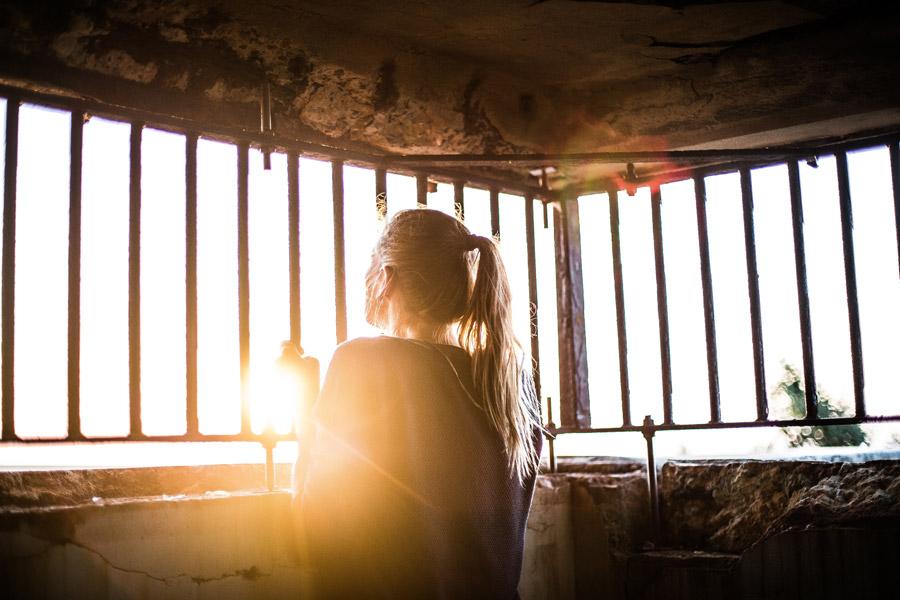 フリー写真 太陽の光と檻の中の外国人女性