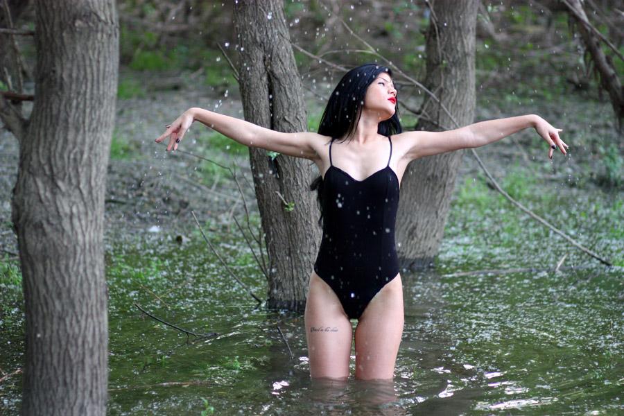 フリー写真 森の沼に入って手を広げる外国人女性