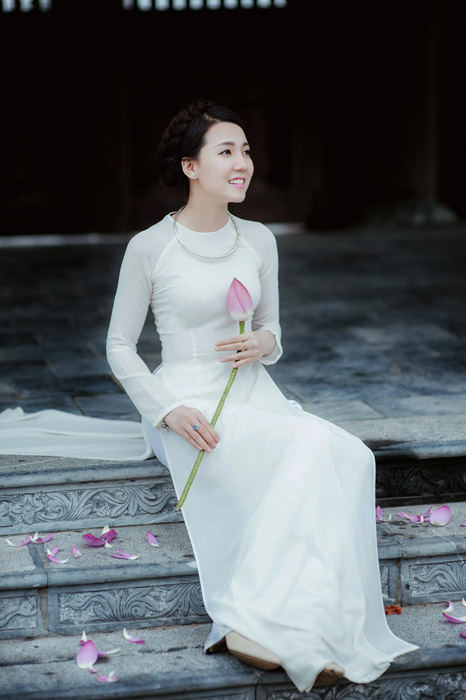 フリー写真 アオザイ姿で蓮の蕾を持つ女性