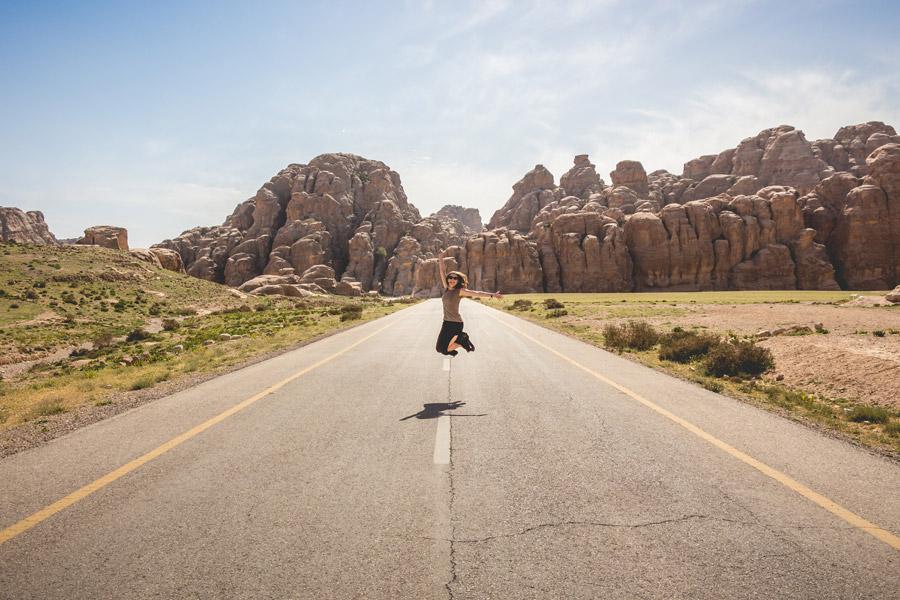 フリー写真 岩山と道路とジャンプする女性