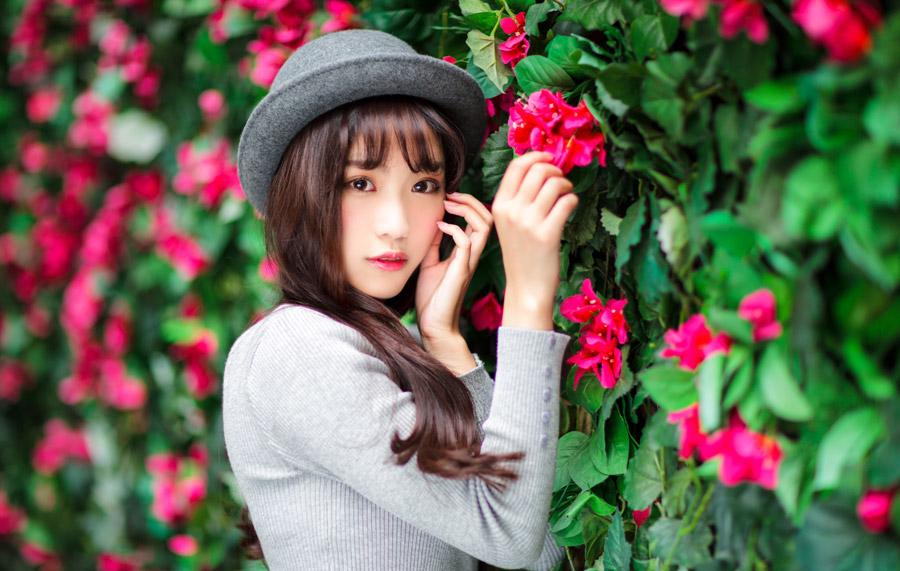 フリー写真 赤色の花とボーラー帽を被る女性のポートレイト