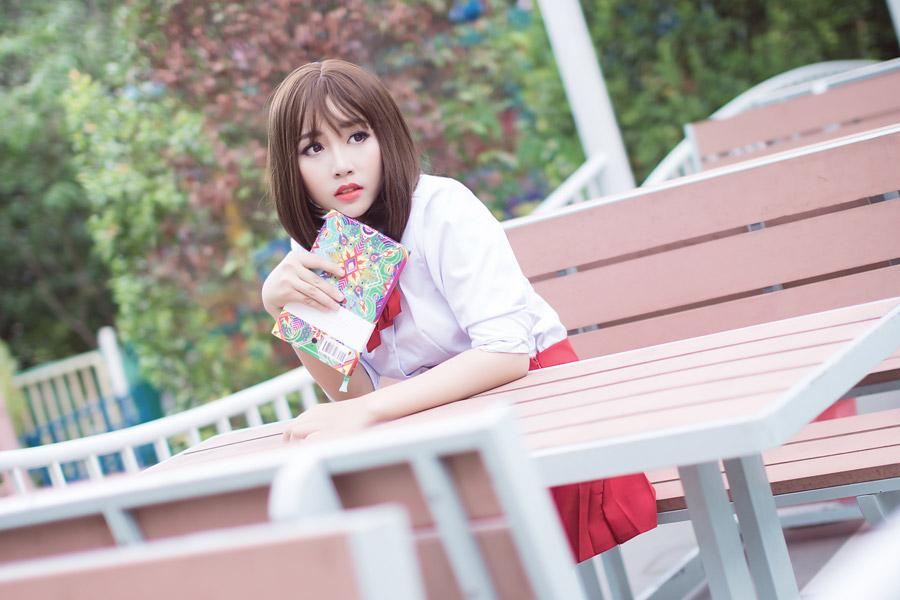 フリー写真 本を持ってベンチに座る女子学生
