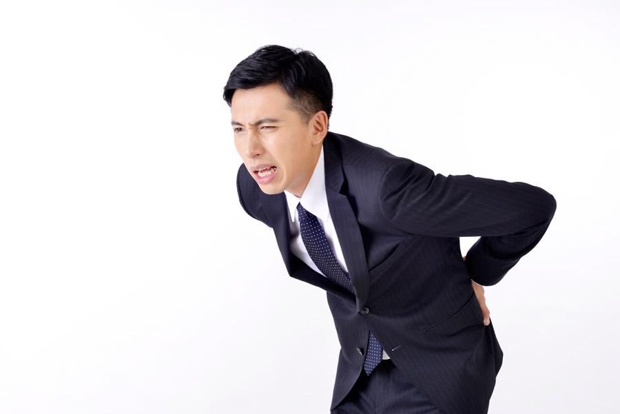 フリー写真 腰痛の日本人ビジネスマン