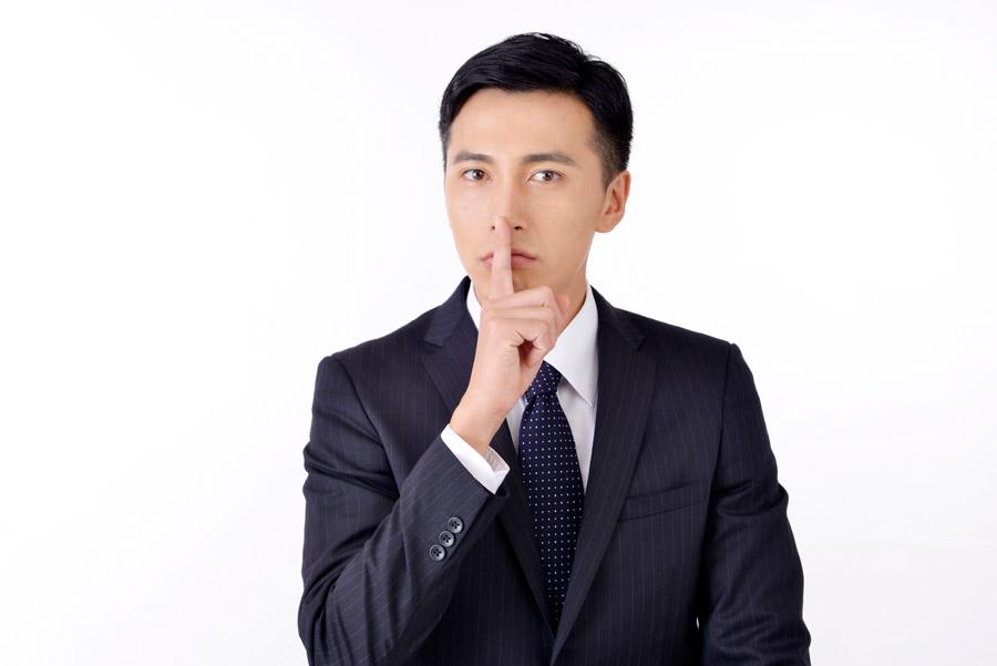 フリー写真 「しーっ!」のポーズの日本人ビジネスマン
