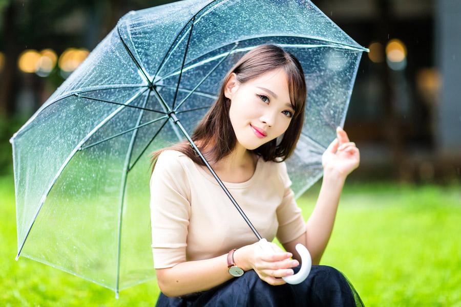 フリー写真 傘を差しながらしゃがんでいる女性