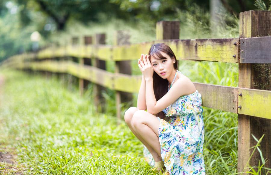 フリー写真 柵の前にしゃがんでいる女性