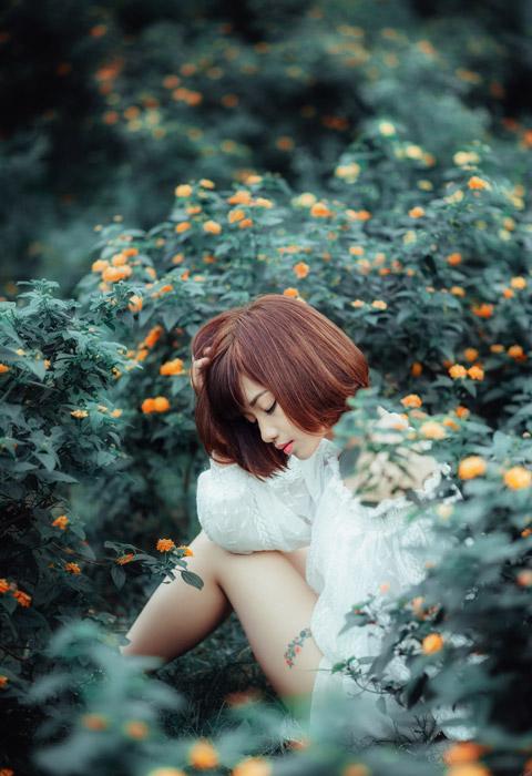 フリー写真 花と頭に手を当てて目を閉じている女性