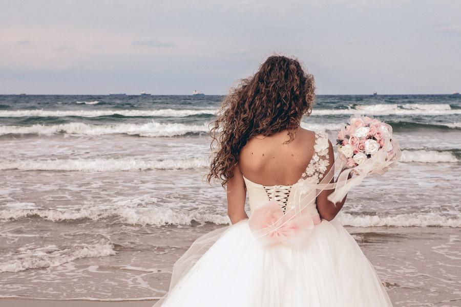 フリー写真 ウェディングドレスを着て海を眺めている花嫁の後ろ姿