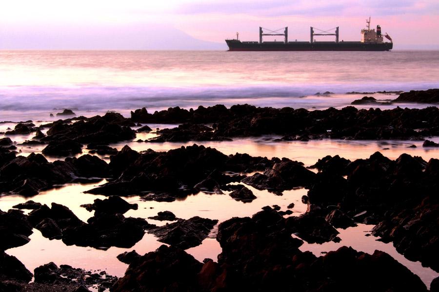 フリー写真 夕暮れの海岸と貨物船