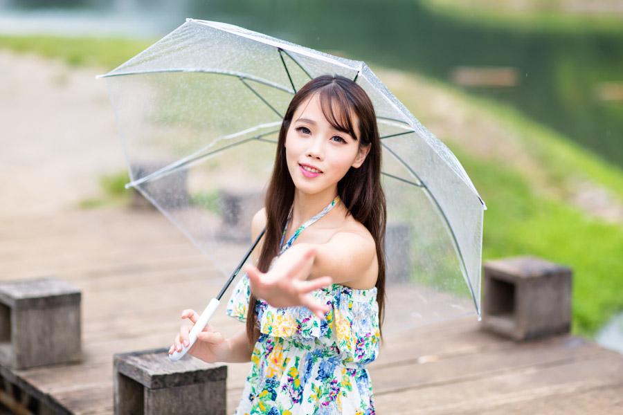 フリー写真 傘を差しながら手を伸ばす女性