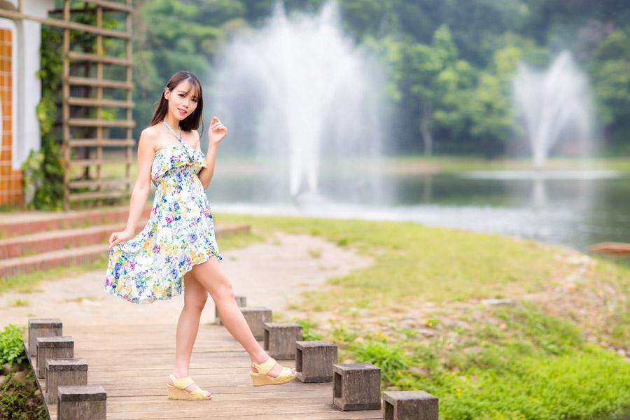 フリー写真 ワンピースの裾をつまんで片足を上げる女性