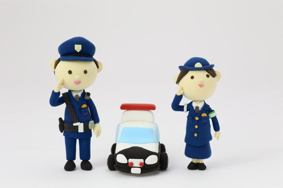 フリー写真 パトカーと敬礼する警察官の人形