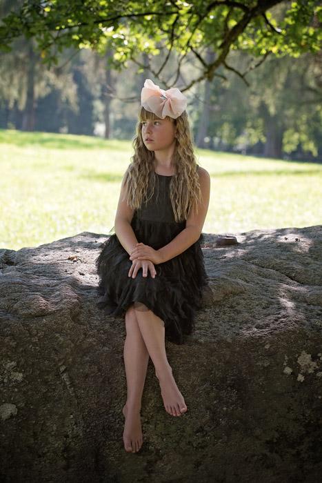フリー写真 岩の上に足を組んで座る外国の女の子