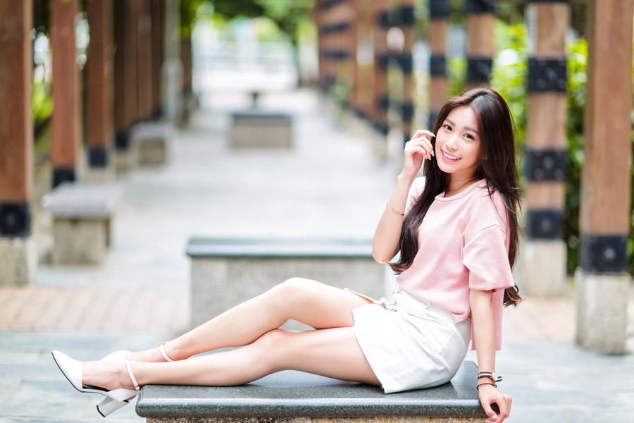 フリー写真 ベンチの上に足を伸ばして座る女性