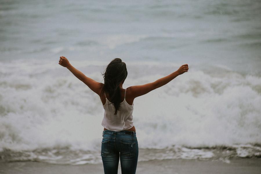 フリー写真 波打ち際に立って手を広げる女性の後ろ姿