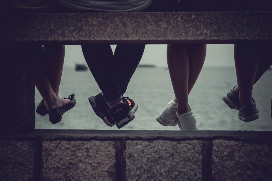 フリー写真 座っている四人の足と海の風景