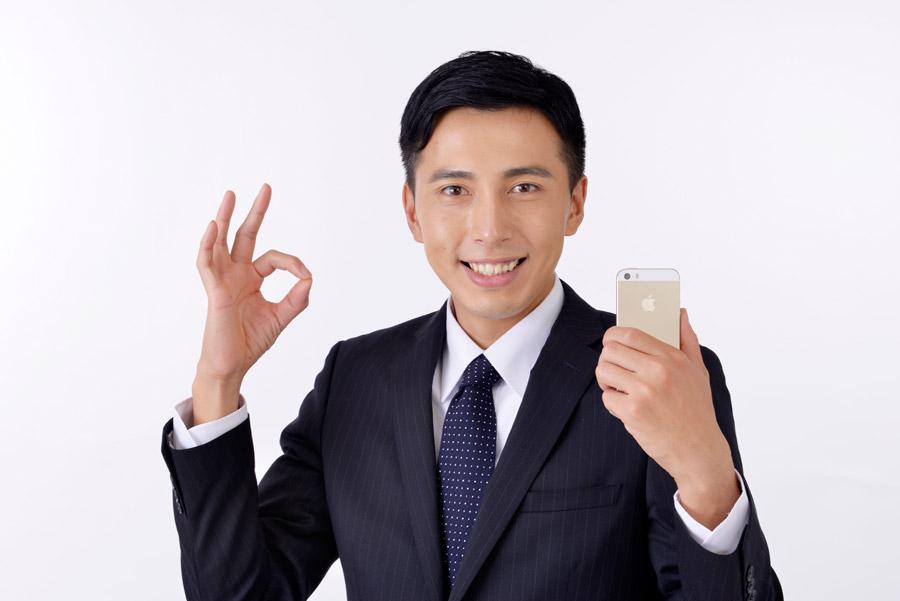 フリー写真 携帯電話を持ってOKサインのビジネスマン