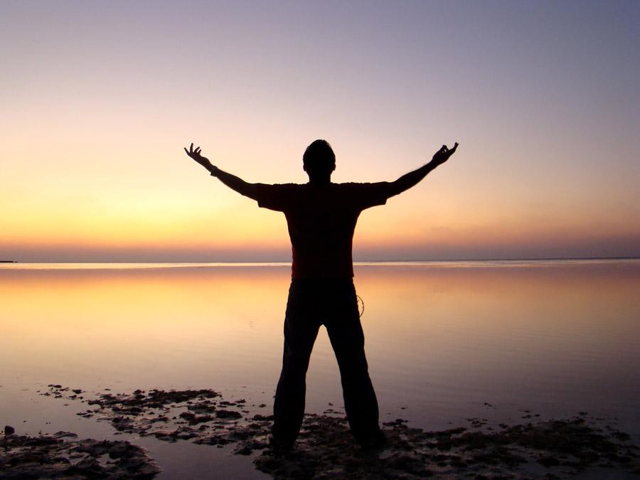 フリー写真 夕暮れの海と手を広げる男性のシルエット
