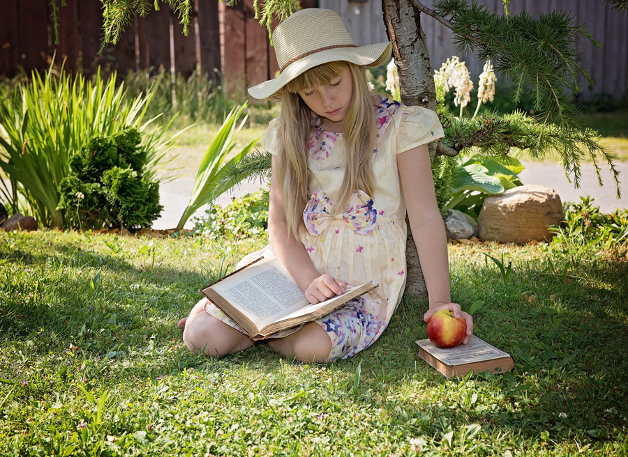 フリー写真 リンゴと本を読んでいる外国の女の子