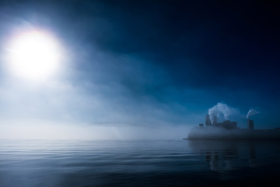 フリー写真 霧のかかる湖と煙が上がる工場の風景