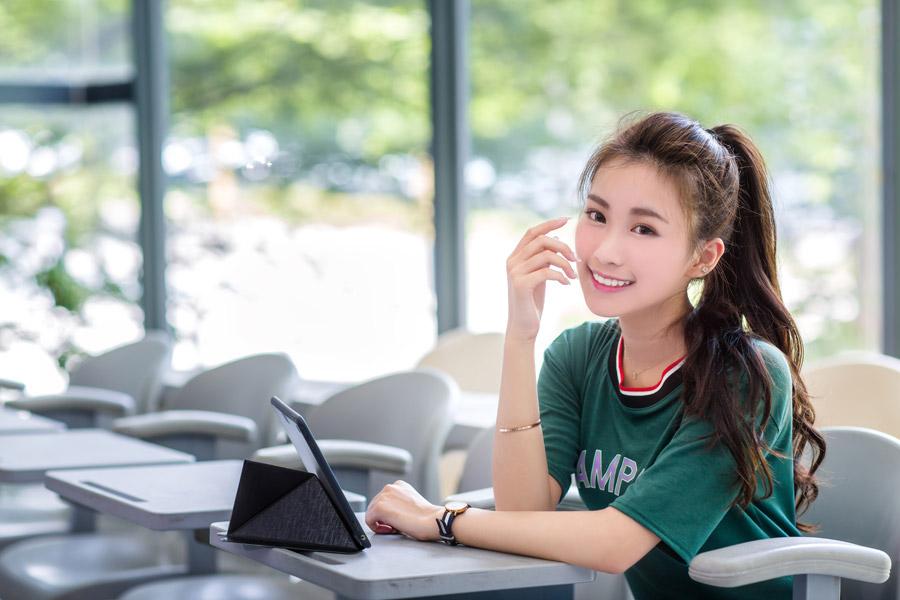 フリー写真 教室の机にタブレットPCを置く女子学生