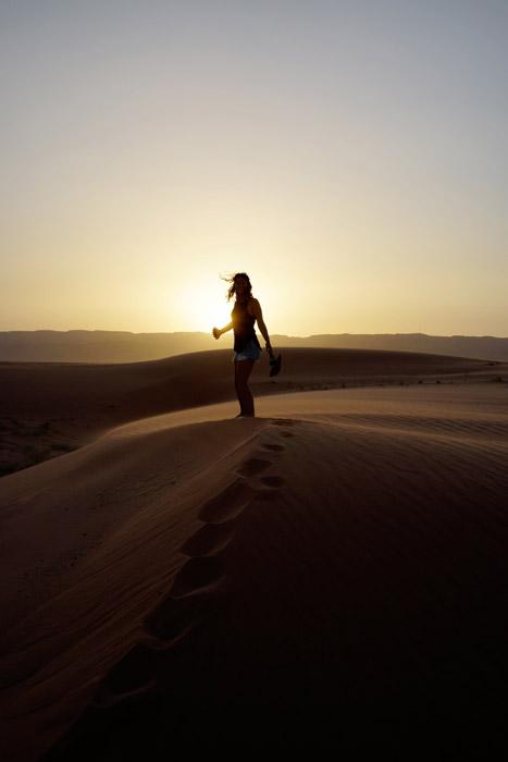 フリー写真 夕日と砂漠に立つ女性