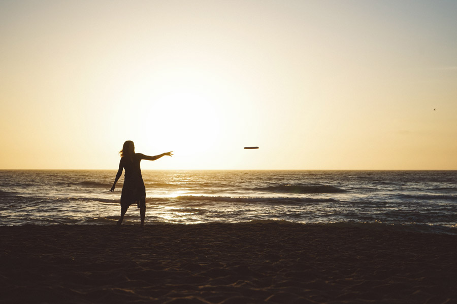 フリー写真 夕暮れのビーチでフリスビーを投げる女性