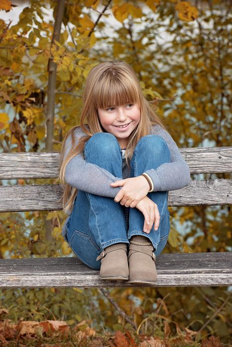 フリー写真 ベンチの上で膝を抱えて座る外国の女の子