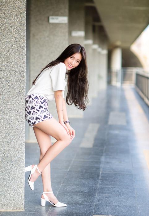 フリー写真 柱に寄りかかって片足を上げる女性