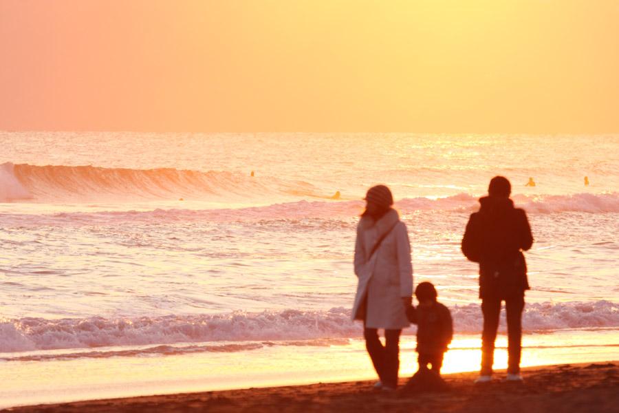 フリー写真 夕暮れの海と三人家族