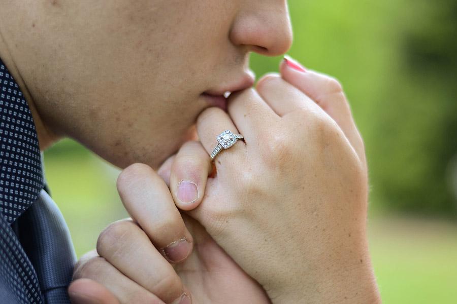 フリー写真 指切りしながら新婦の手にキスをする新郎