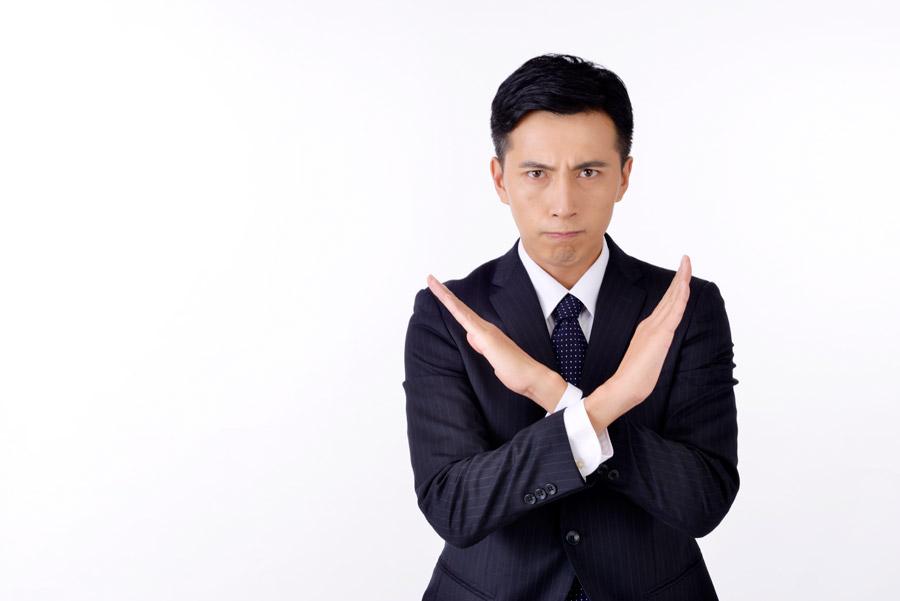フリー写真 腕をクロスさせてバツを作る日本人のビジネスマン