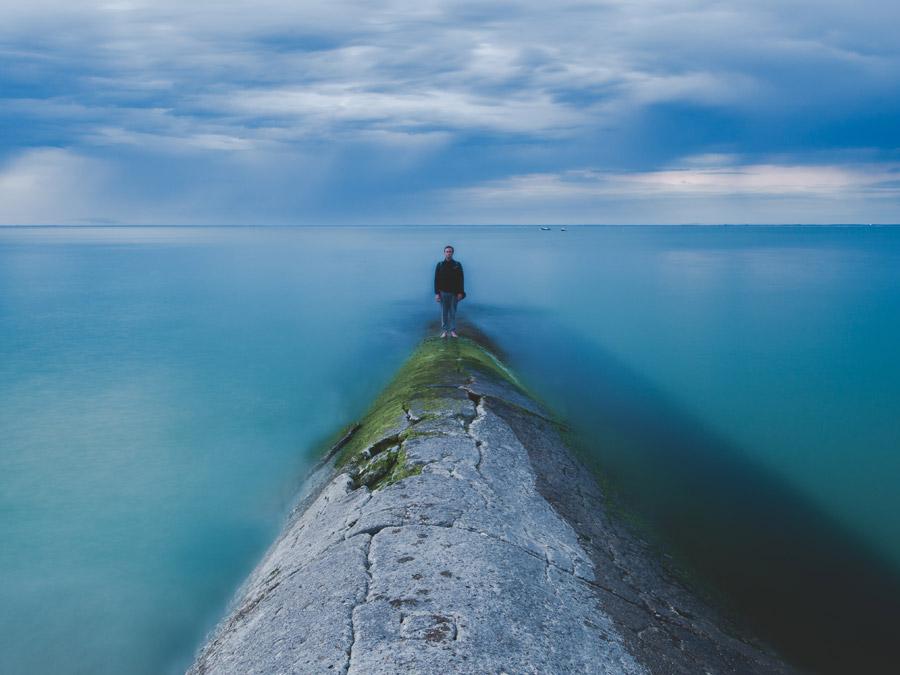 フリー写真 海と堤防の先に立つ男性