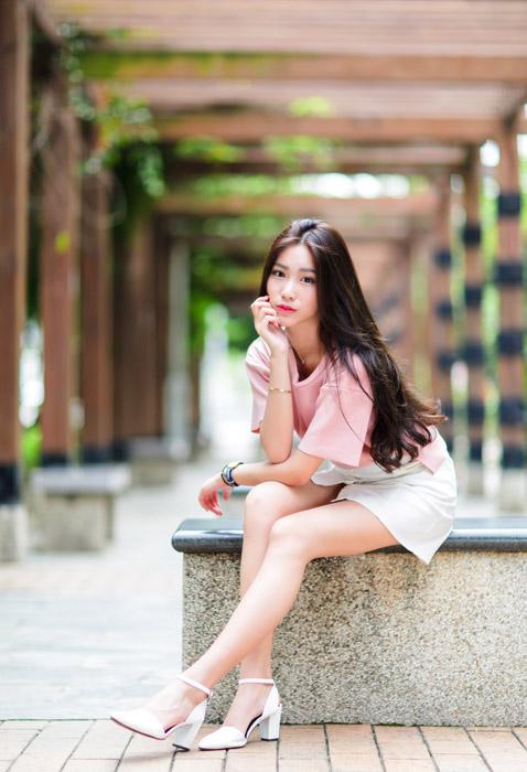 フリー写真 ベンチに座って頬杖をつく女性のポートレイト