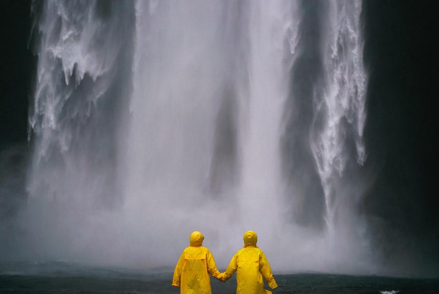 フリー写真 滝の前で手をつなぐ二人の人物の後ろ姿