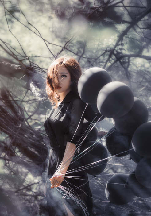 フリー写真 黒色の服を着て黒色の風船を持つ女性