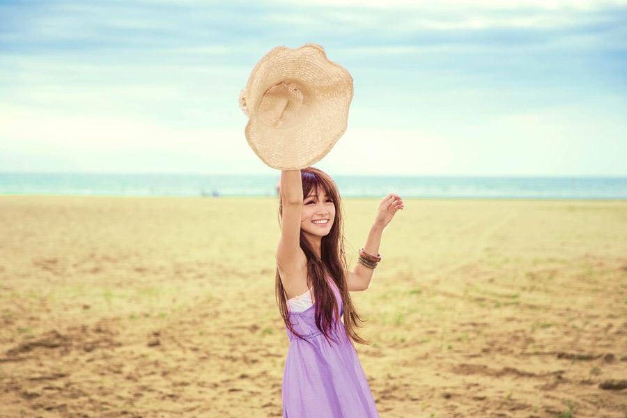 フリー写真 砂浜で麦藁帽子を持つ女性
