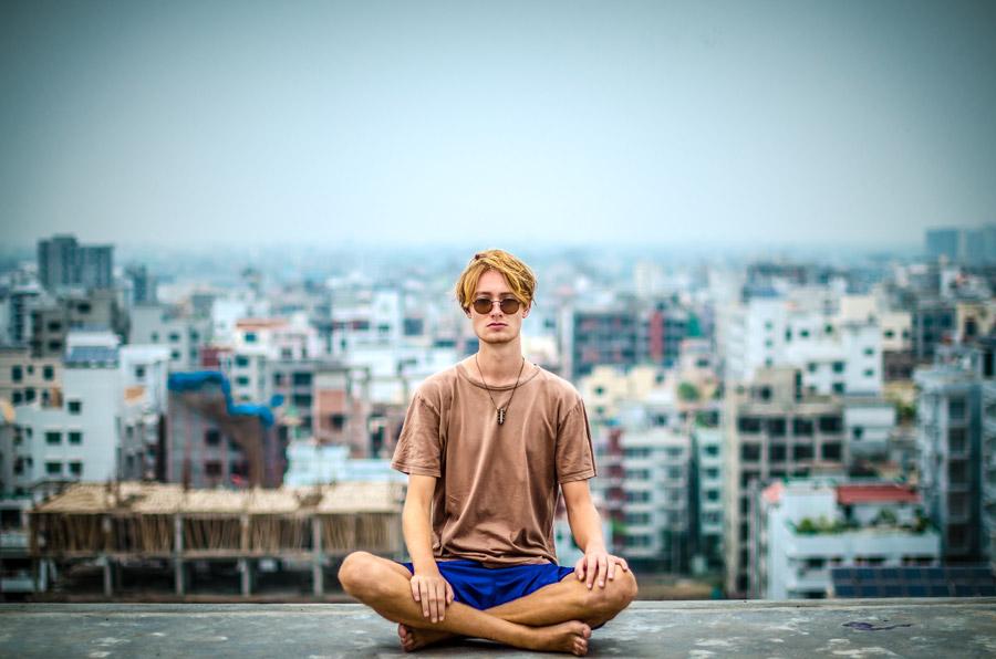フリー写真 バングラデシュの街並みと坐禅を組む外国人男性