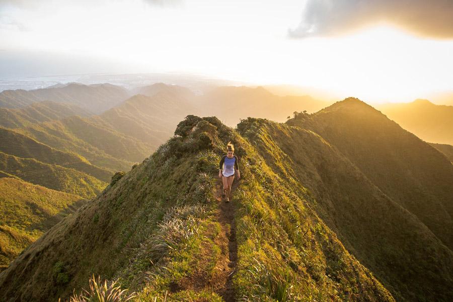 フリー写真 夕陽と山の上を歩いている外国人女性